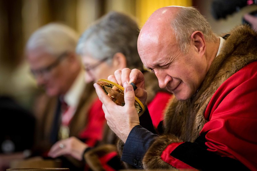Prime Warden Richard Fox examines a coin at the 2020 Trial of the Pyx