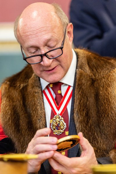 Second Warden Richard Fox examines a commemorative coin at the Trial of the Pyx 2019