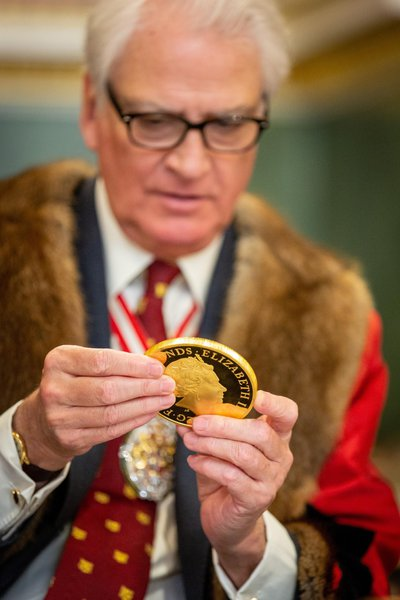 Prime Warden Michael Prideaux examines a gold commemorative coin. Image: © The Goldsmiths' Company. Photograph: Richard Lea-Hair
